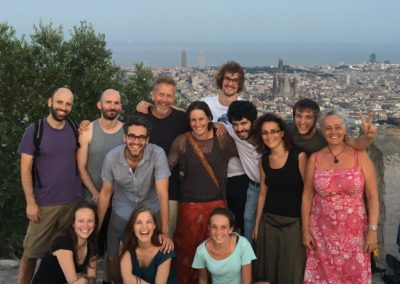 a group of people are standing in front of a city panorama with their arms around each other, smiling
